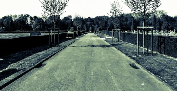 Longue rue calme près d'un cimetière. Long calm road alongside a graveyard / cemetery.